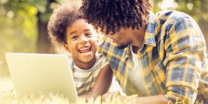 Technology can be fun. African American father and his daughter using laptop in park. Close up.