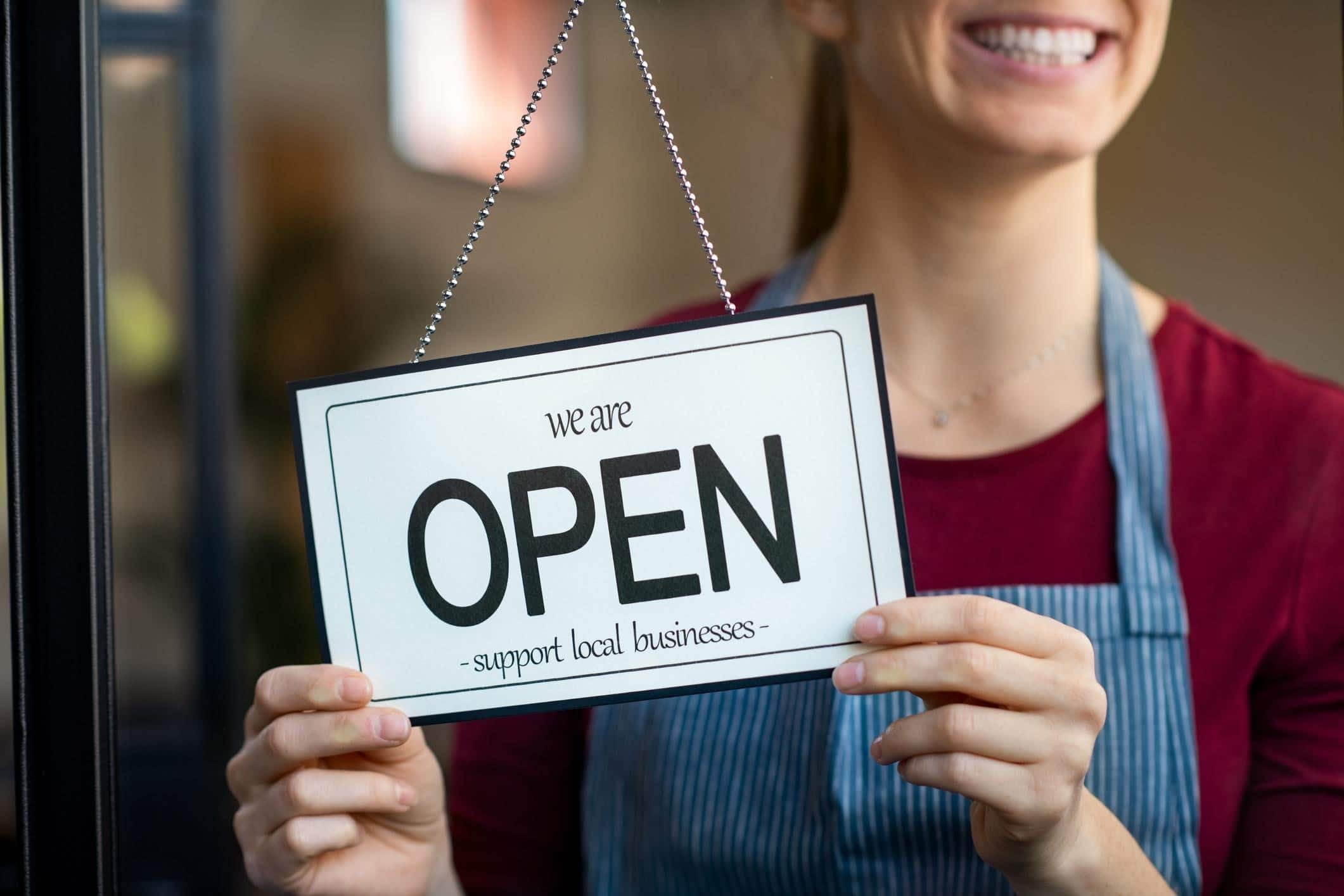 "Small business owner flips sign to ""open"" in her store."