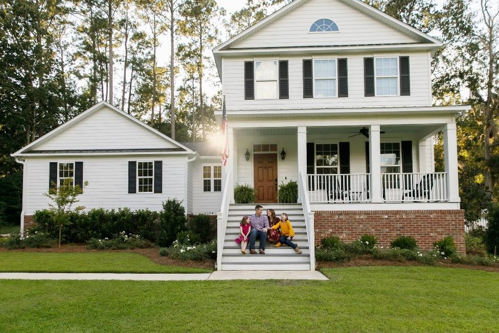 Family sits on the front steps of their brand new home.