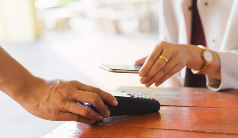 Woman uses mobile wallet to make a purchase.