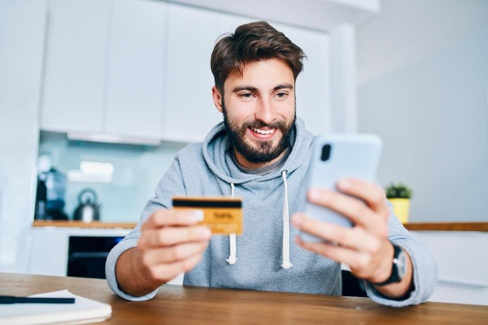 Young man uses smartphone and personal banking card to make an online purchase.