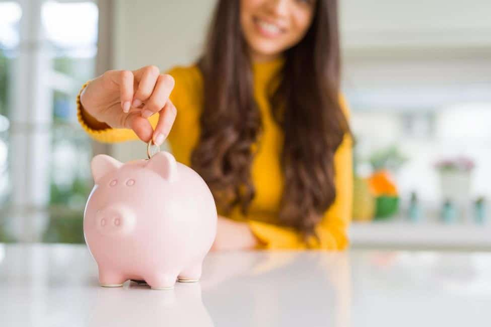 Woman drops coin into pink piggy bank to save money.
