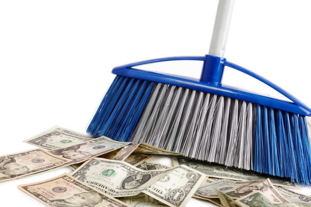 A broom sweeping a pile of dollar bills on the floor