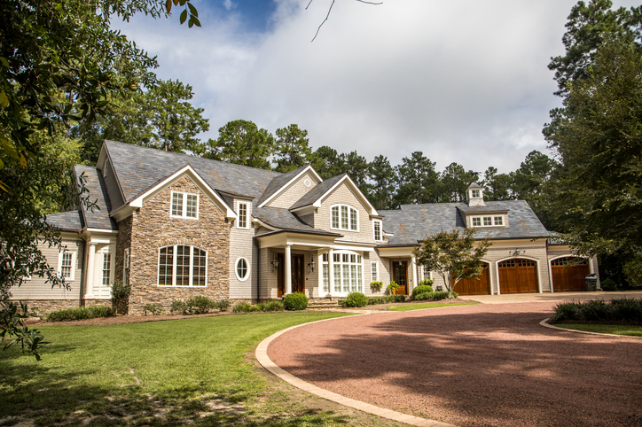 Front view of large estate home in the south with a gravel driveway and many windows.