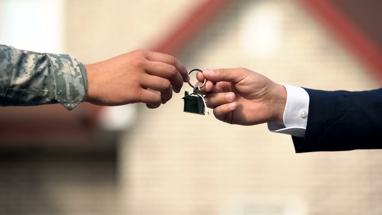 Man in business suit giving house key to man in military uniform.
