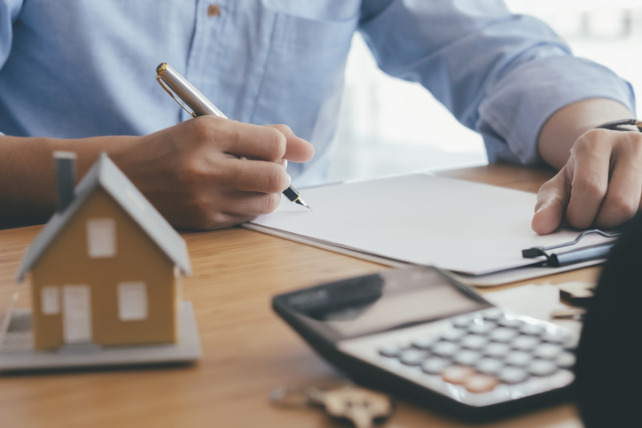 Young man is signing financial mortgage contract of sale for a new house with real estate agent at office.