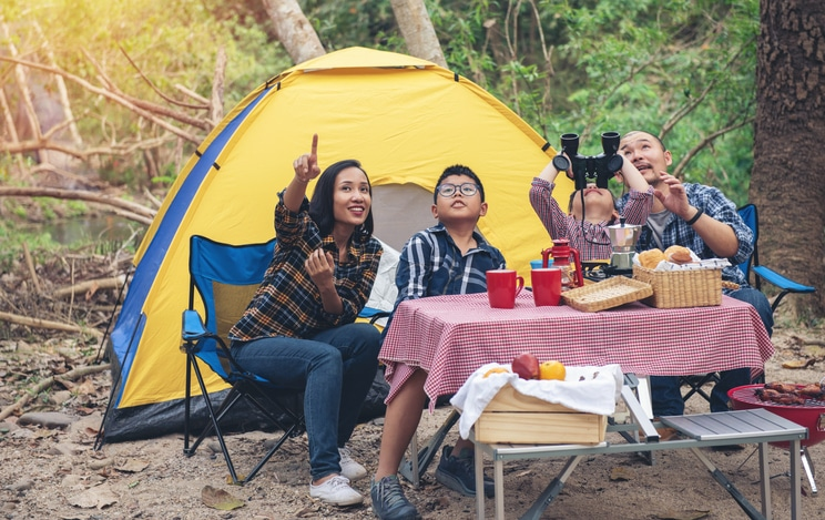 A happy family camping and looking birds with binoculars.