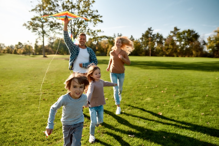 Cheerful parents with two kids running with kite in the park on a sunny day.
