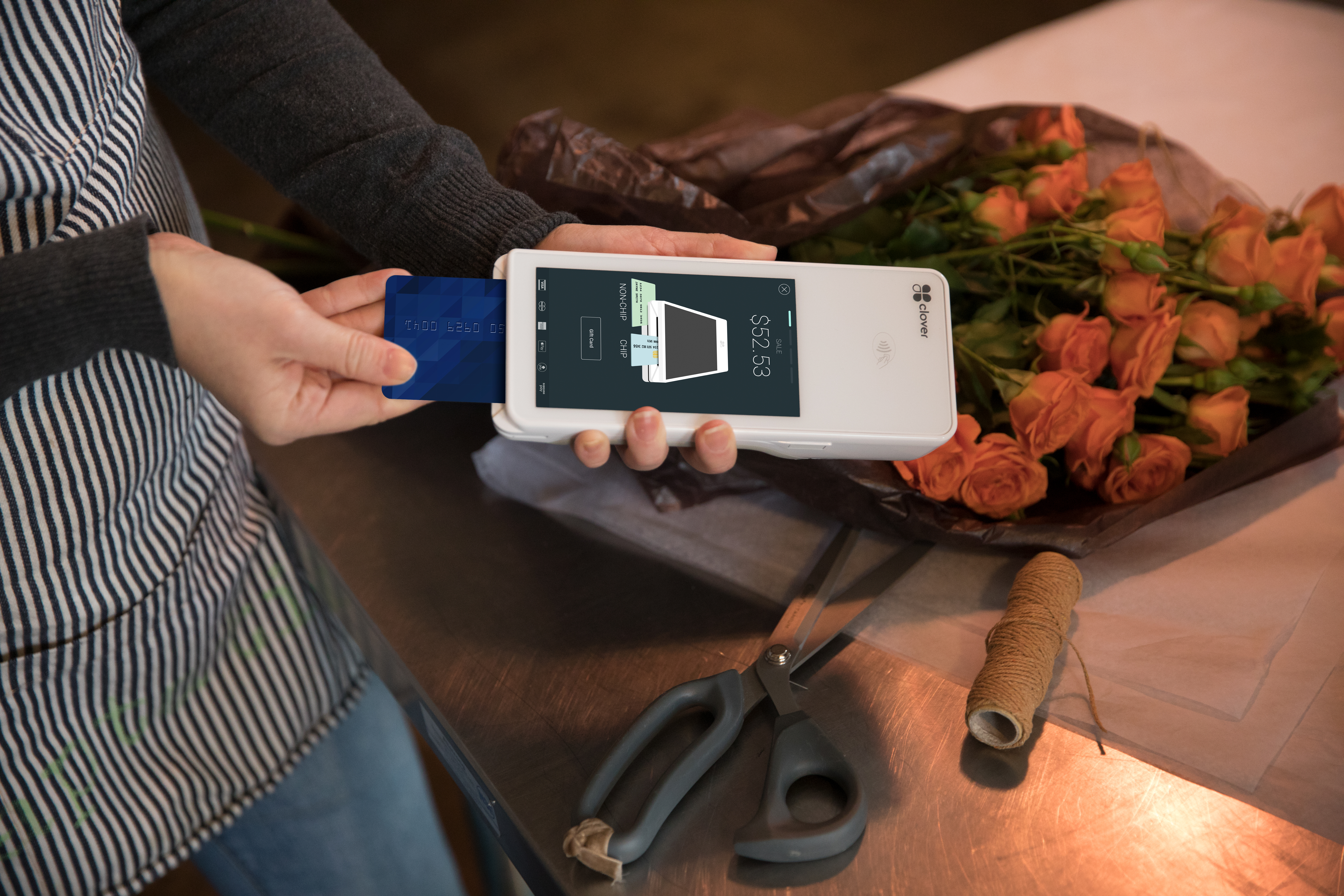 A woman inserting her credit card into a Clover Flex mobile point-of-sale device from Clover.